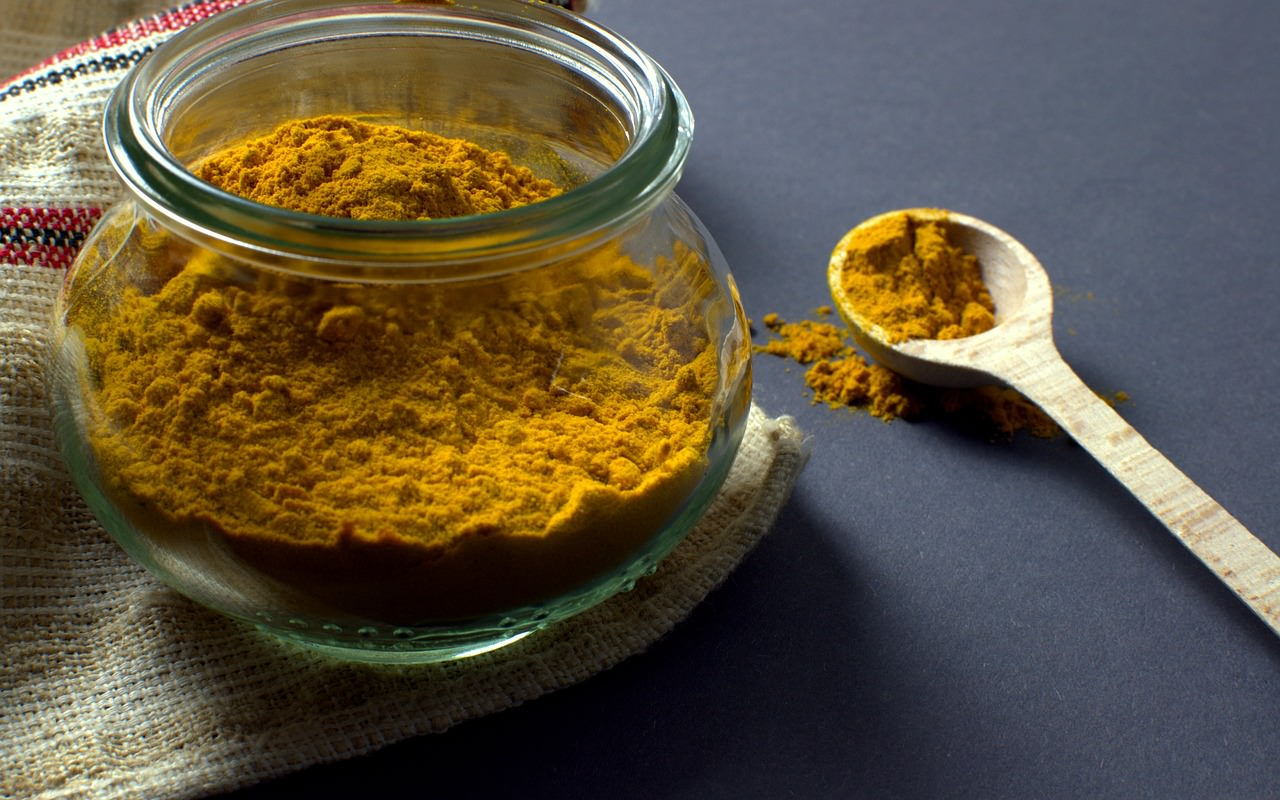 Image of turmeric in a glass jar and in a wooden spoon