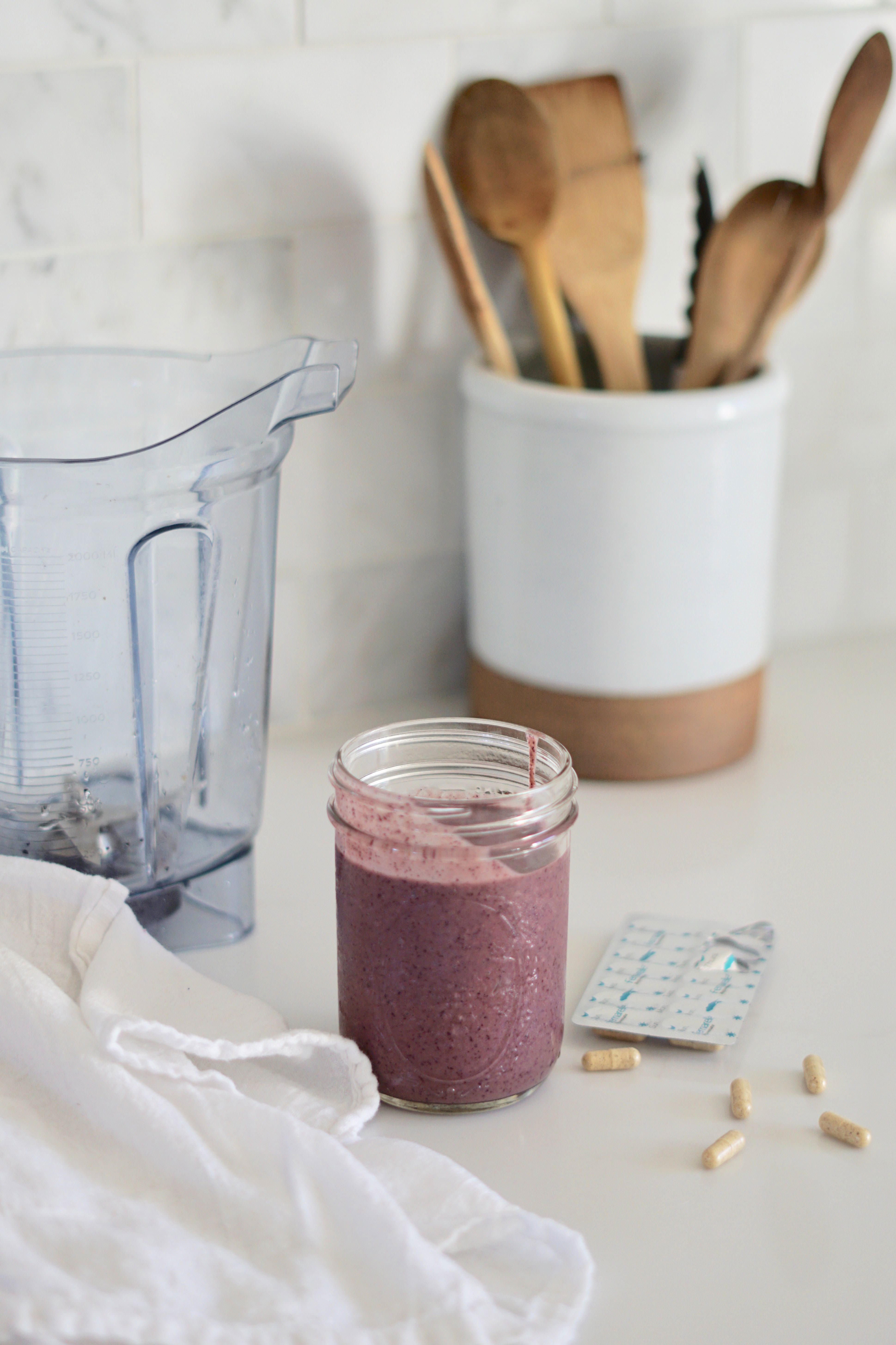 Photo of a fruit shake and supplements on a kitchen table