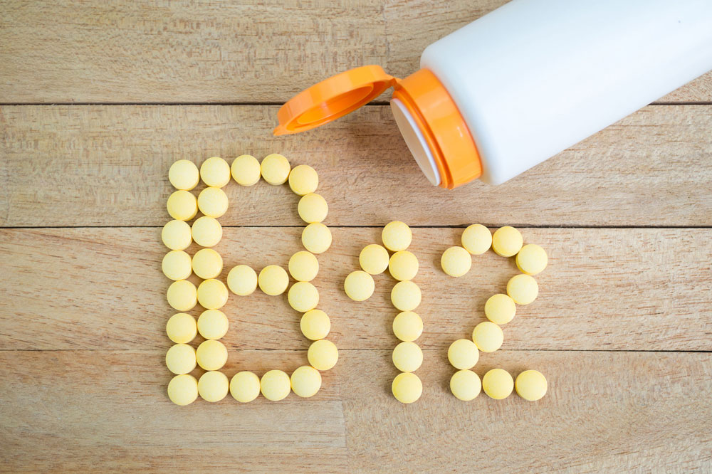 Image of a bottle and pills on a wood table spelling out 'B12'