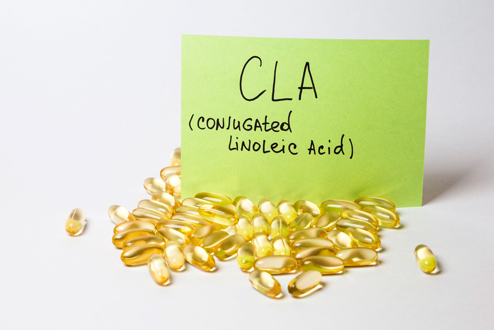 Image of softgels and a piece of paper that says 'CLA (conjugated linoleic acid)' on a table