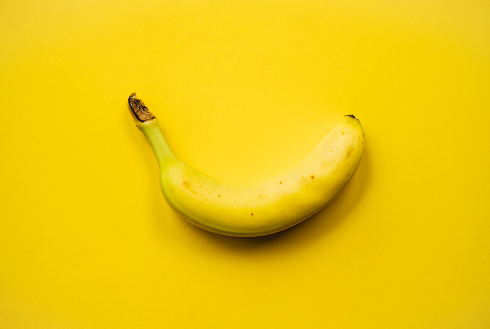 Image of a banana on a yellow background, a good source of potassium