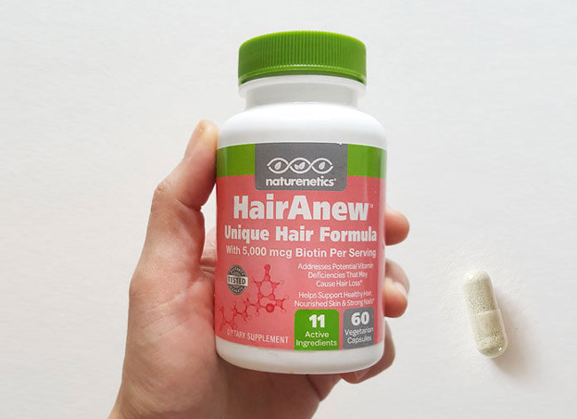 Image of a bottle of HairRenew and a capsule on a white table