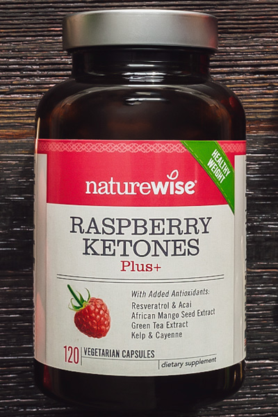Image of a bottle of NatureWise Raspberry Ketones Plus+ on a dark wood table